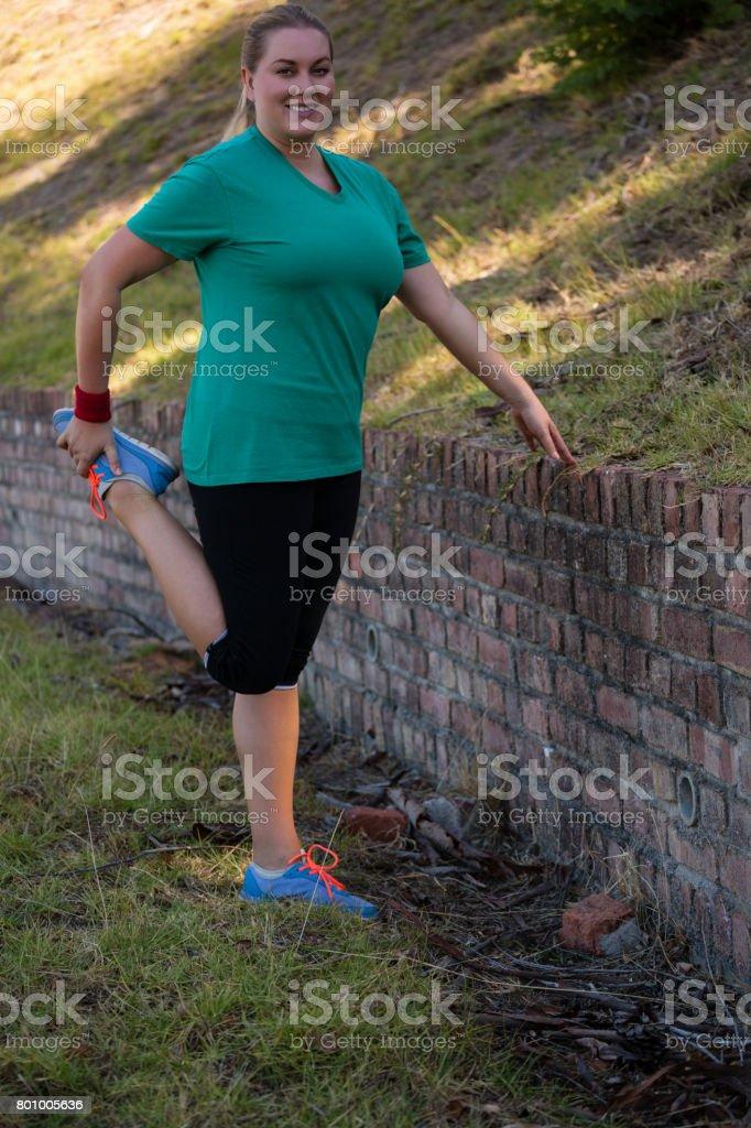 Frau, die Durchführung von stretching-Übung beim Hindernis-Parcours-training – Foto