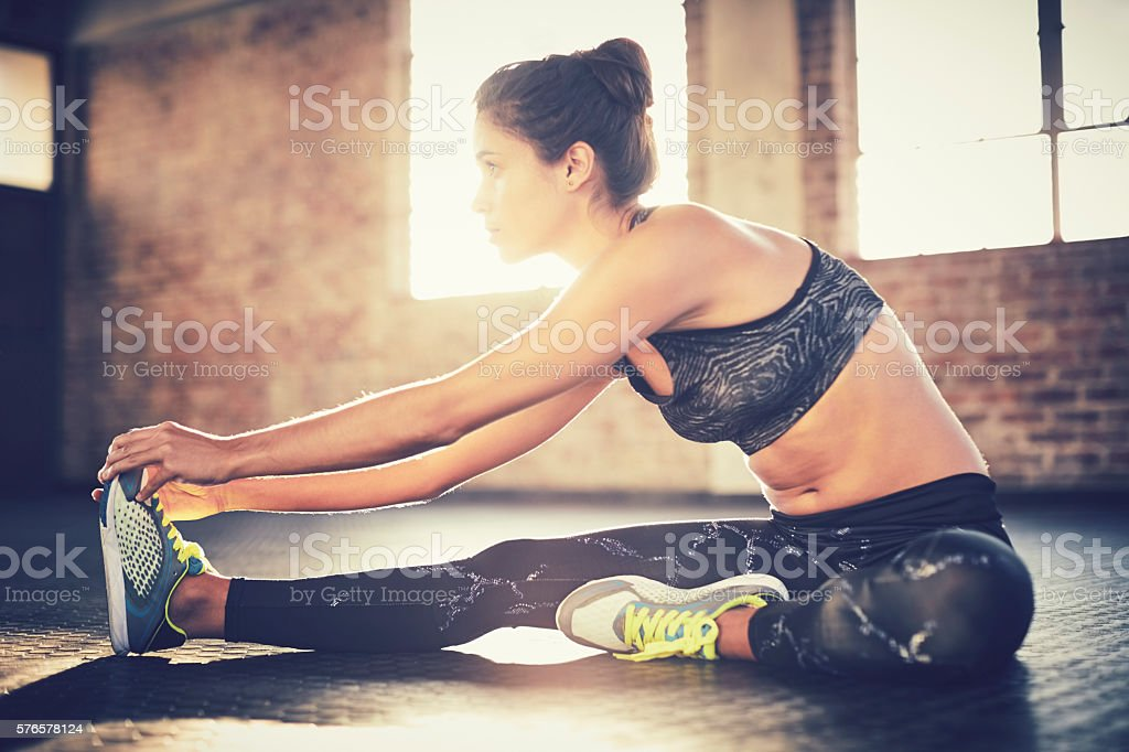 Woman performing stretching exercise in gym stock photo