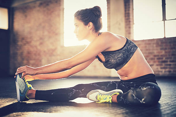 Woman performing stretching exercise in gym Side view of woman performing stretching exercise in gym. Young female is touching toe on floor. She is sitting in health club. touching toes stock pictures, royalty-free photos & images