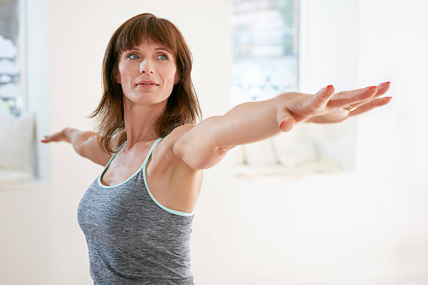 Woman performing yoga in warrior pose Portrait of mature woman stretching her arms and looking away at gym. Beautiful woman performing yoga in warrior pose, Virabhadrasana. one mature woman only stock pictures, royalty-free photos & images