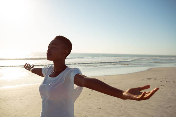 Woman performing yoga on the beach Front view of young African-american woman performing yoga on the beach arms outstretched stock pictures, royalty-free photos & images