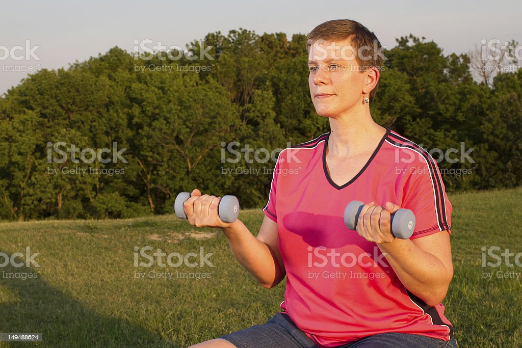 Woman performs dumbell curls outside on the grass. royalty-free stock photo