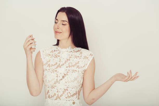 woman perfume portrait in white dress female model aroma smell. - spruzzo profumo foto e immagini stock