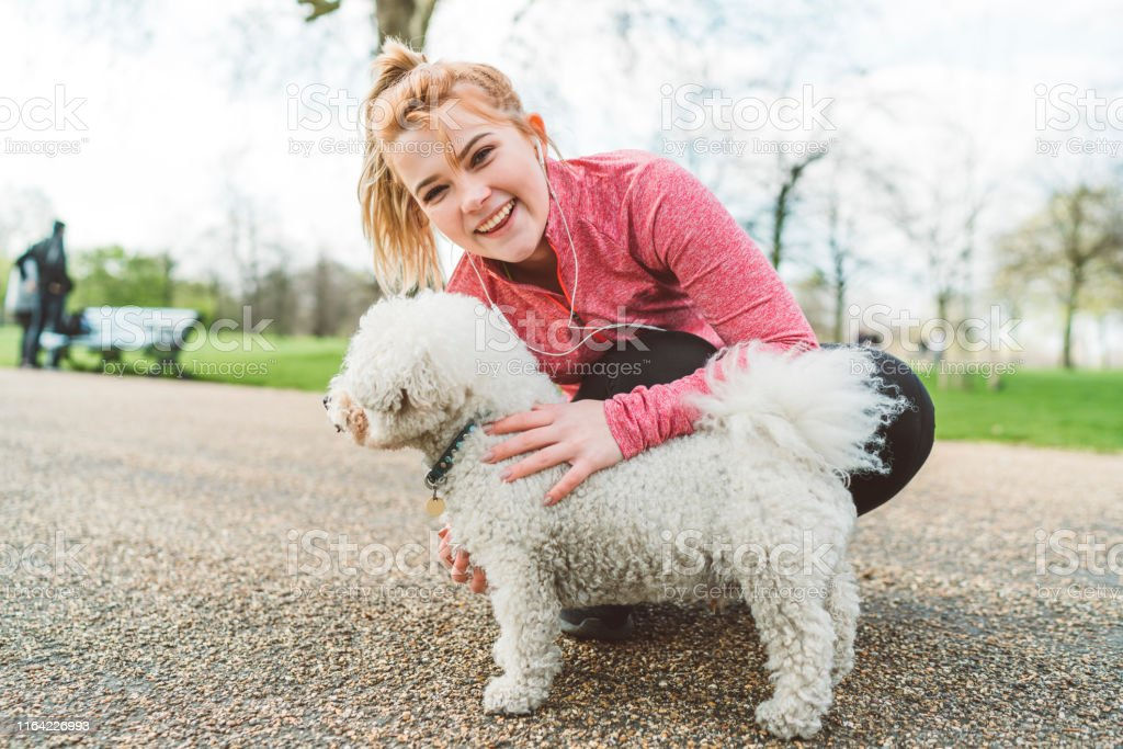 Young woman in sportswear, jogging in London on a sunny day. Petting...