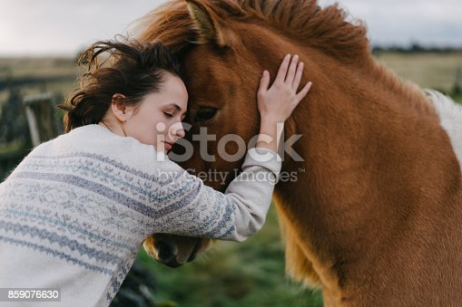 Young Caucasian woman petting Icelandic horse  on the meadow