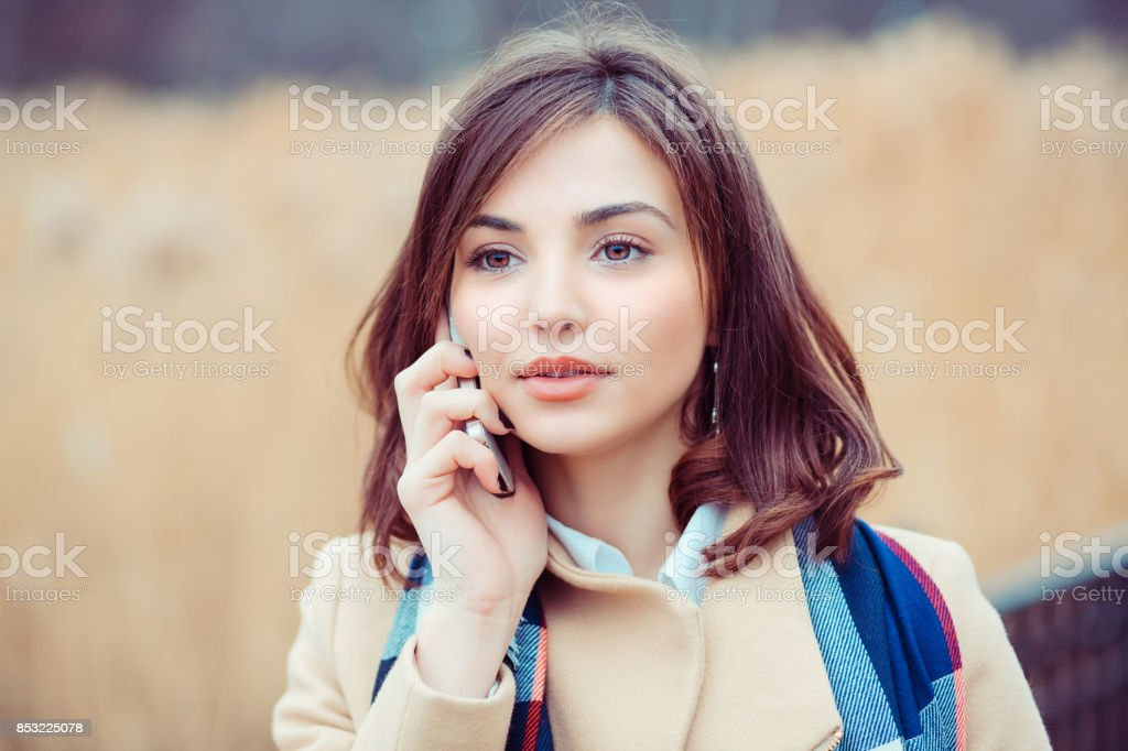 Woman phone talking. Closeup young happy beautiful woman girl lady talking on mobile cellphone looking up thinking isolated park city scape outdoor background. Positive face expression human emotion stock photo