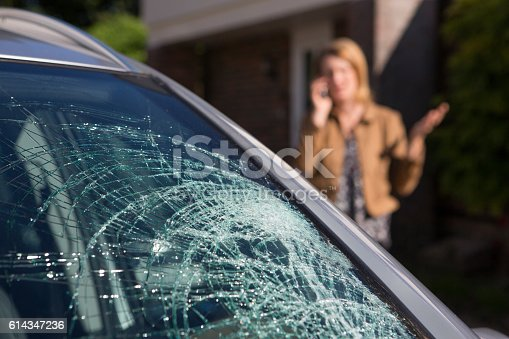 istock Woman Phoning For Help After Car Windshield Has Broken 614347236