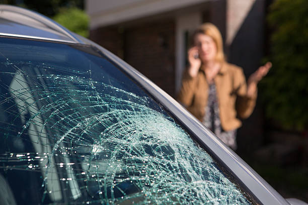 kobieta dzwoni za pomoc po przedniej szybie samochodu złamał - popękany zdjęcia i obrazy z banku zdjęć