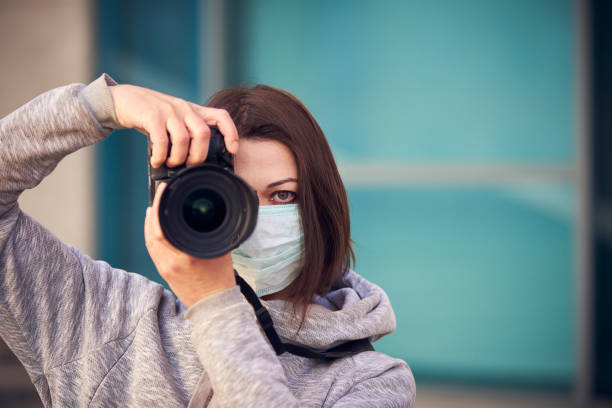 Woman photographer in mask with camera on street because epidemic of coronavirus in city. Protection against virus and infection stock photo