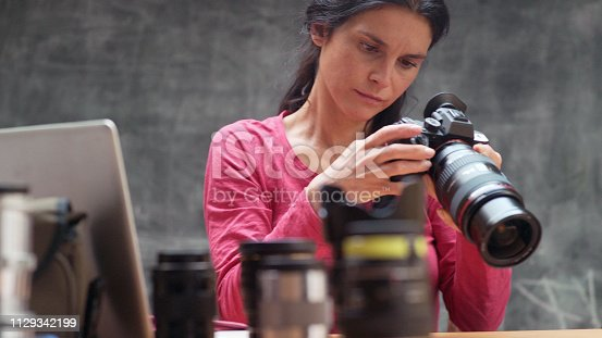Stock image of a woman photographer in her 30s 40s checking over her camera & lenses in preparation for a shoot.