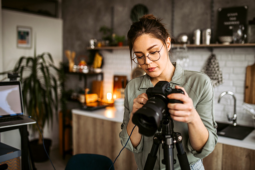 Young pretty female photographer preparing photographic equipment for food photography shooting in home studio