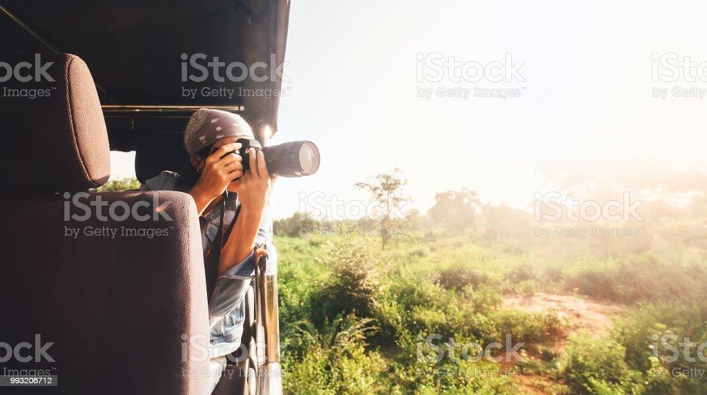 女攝影師拍攝的照片與專業相機從旅遊車輛在熱帶野生動物園 - 免版稅亞洲圖庫照片