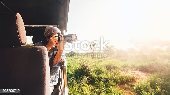 Woman photographer takes a picture with professional camera from touristic vehicle on tropical safari