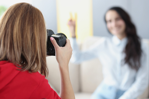 Woman photographer takes pictures of girl on couch. Training profession photographer concept