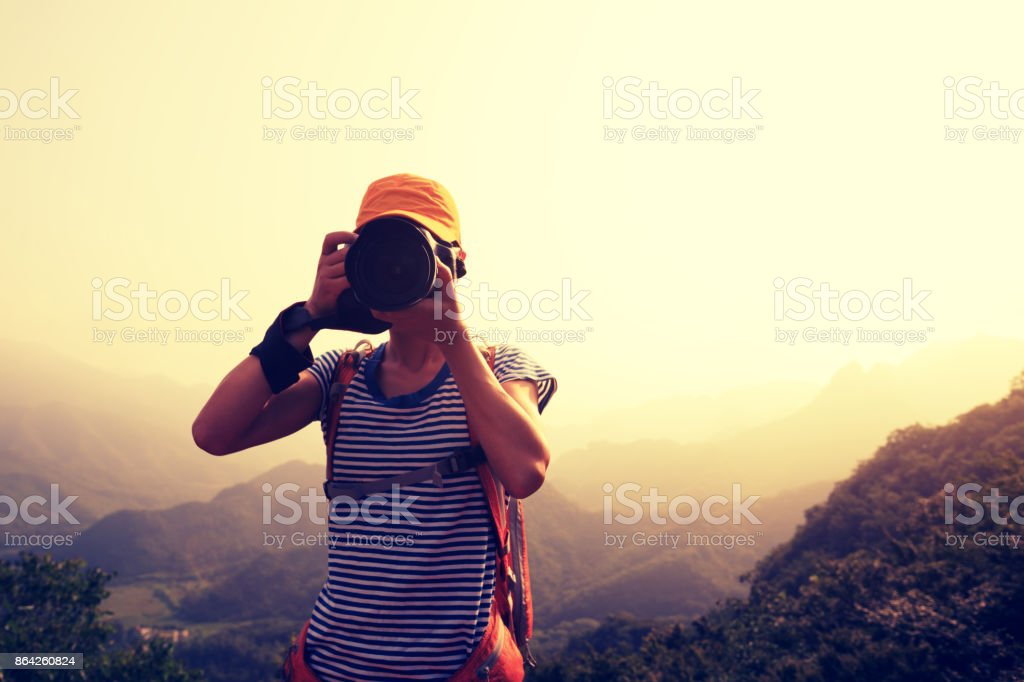woman photographer  taking photo on top of mountain royalty-free stock photo