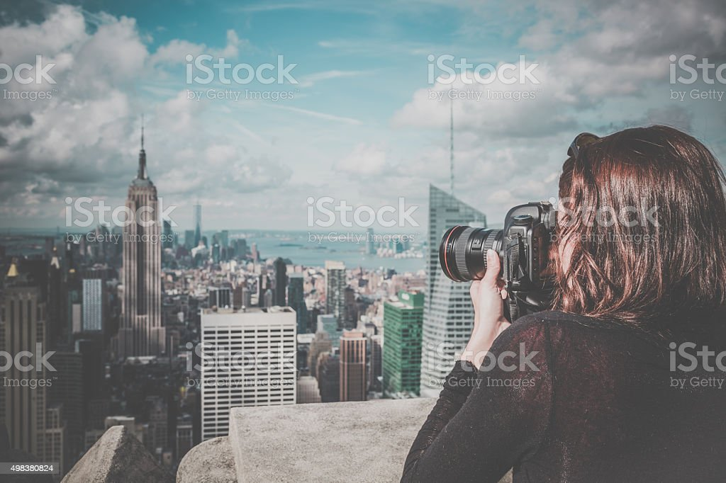 woman photographer taking picture of the Empire State Building stock photo