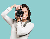 Beautiful girl photographer is taking pictures with dslr camera. Isolated on grey background