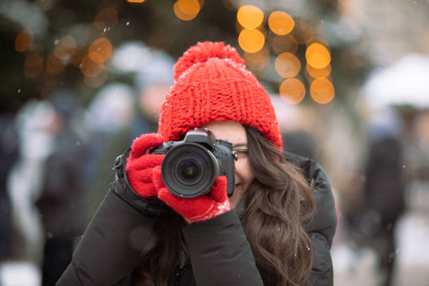 woman photographer with professional camera shooting outdoors at winter time christmas tree on background stock photo