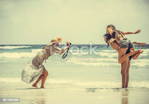 Woman photographer working with couple on the tropical beach