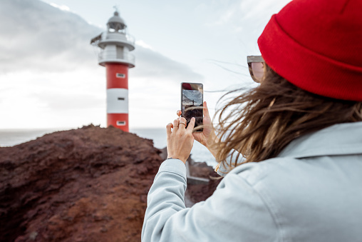 Woman photographing breathtaking views on the rocky coast