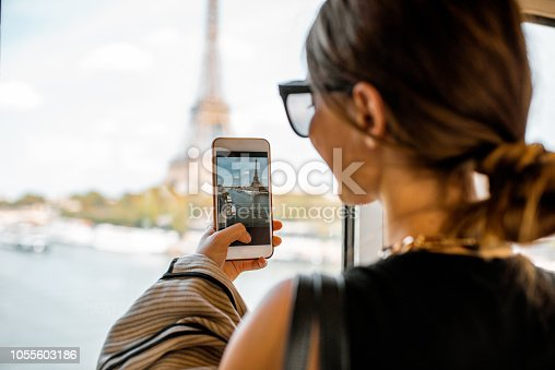 Young woman photographing with smartphone Eiffel tower from the subway train in Paris. Image focused on the phone