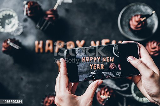 Female hands taking photograph of Happy New year text cookie with mobile phone. Woman photographing flat lay new year cookies and cupcakes on black background.