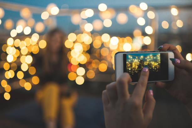 Frau fotografieren Freunde auf Party auf dem Dach – Foto