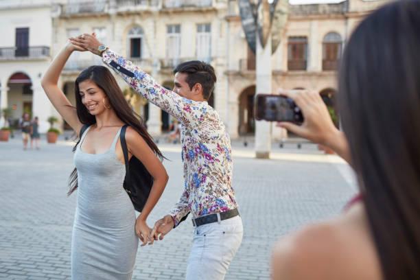 frau fotografieren freunde tanzen in stadt - urlaub in kuba stock-fotos und bilder
