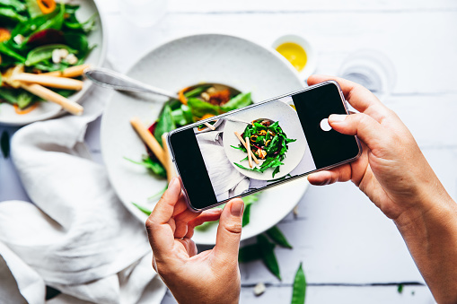Woman taking photograph of a healthy green salad with her cell phone. Close-up of female hands photographing a plate of salad with mobile phone.