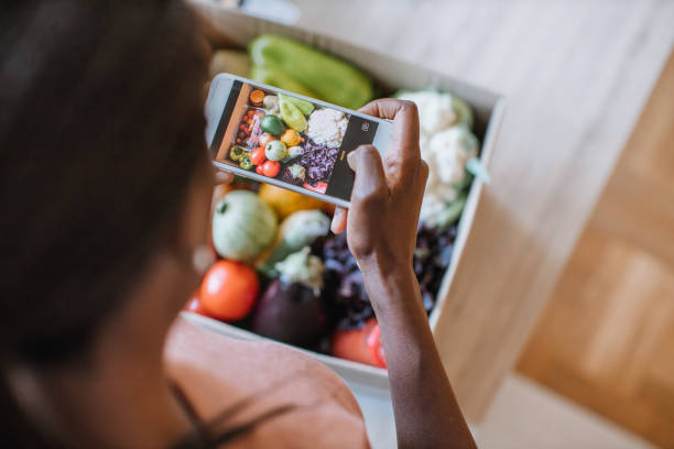 Woman Photographing Groceries In Meal Kit stock photo