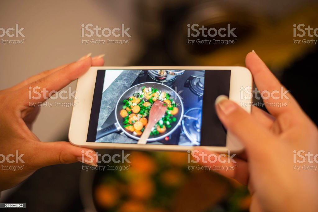 Woman photographing healthy meal in kitchen with smart phone stock photo