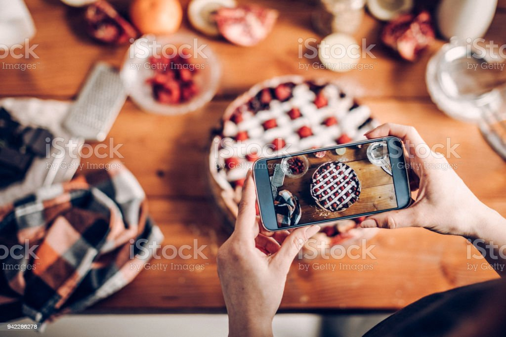 Woman photographing her cake stock photo