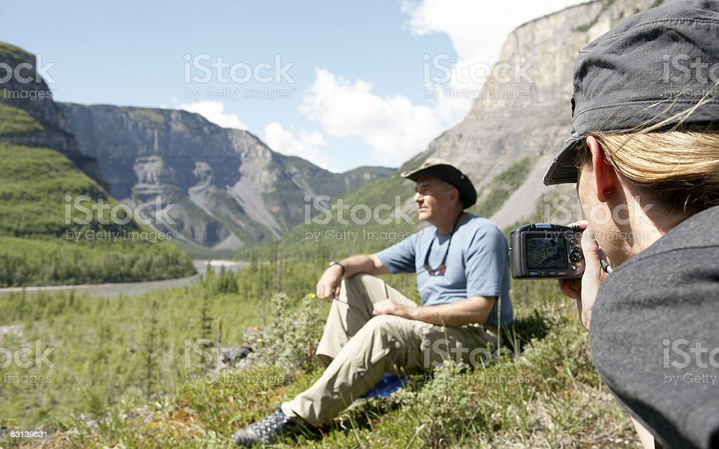 woman photographing man sitting on grassy hill royalty free stockfoto