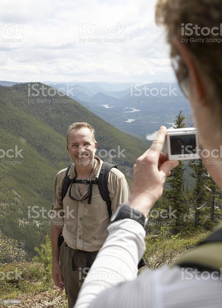 woman photographing man with mountain view behind royaltyfri bildbanksbilder