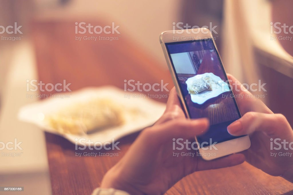 Woman photographing pancakes at home stock photo