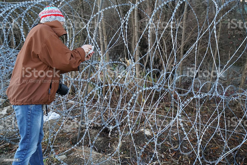 Woman photographing razor wire on border in Slovenia stock photo