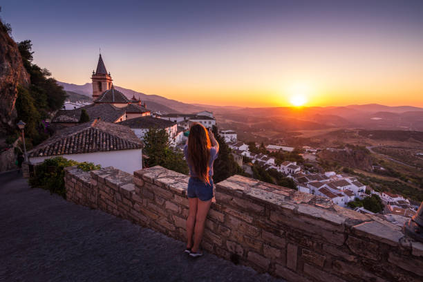 Woman photographing sunset from Zahara de la Sierra in Spain stock photo