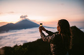 One woman, standing high on beautiful mountain Batur in sunset alone, photographing sunset and volcano with smart phone.