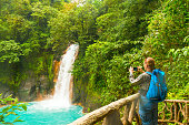 Mature women photographing the turquoise river waterfall from high up.