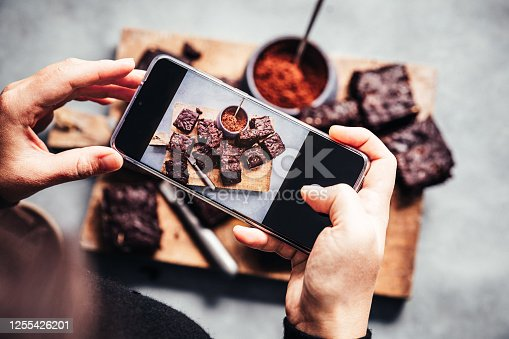 Point of view of a woman taking photos of fresh made chocolate zucchini brownies with her mobile phone. Female photographing vegan brownies in kitchen.