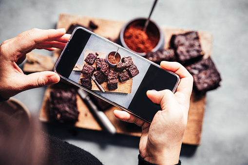 Woman photographing vegan brownies