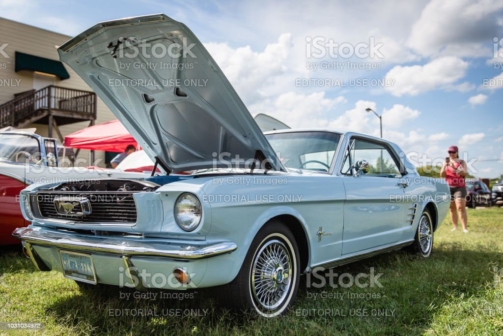 A woman photographs a restored vintage Ford Mustang at the Matthews Auto Reunion stock photo