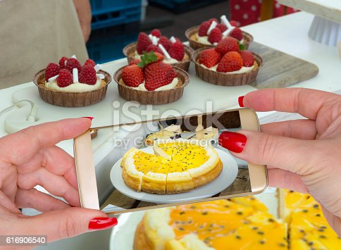 Personal perspective of mature woman photographing a Mango cheesecake with passionfruit sauce on her gold phone in a baking tent on a market, and she uploads it to social media friends before tasting it. Or is she going for the smaller strawberry tarts