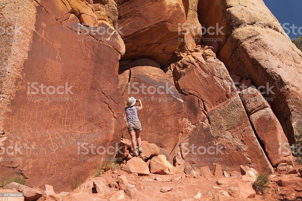 Woman photographs petroglyphs Vermilion Cliffs National Monument Arizona stock photo