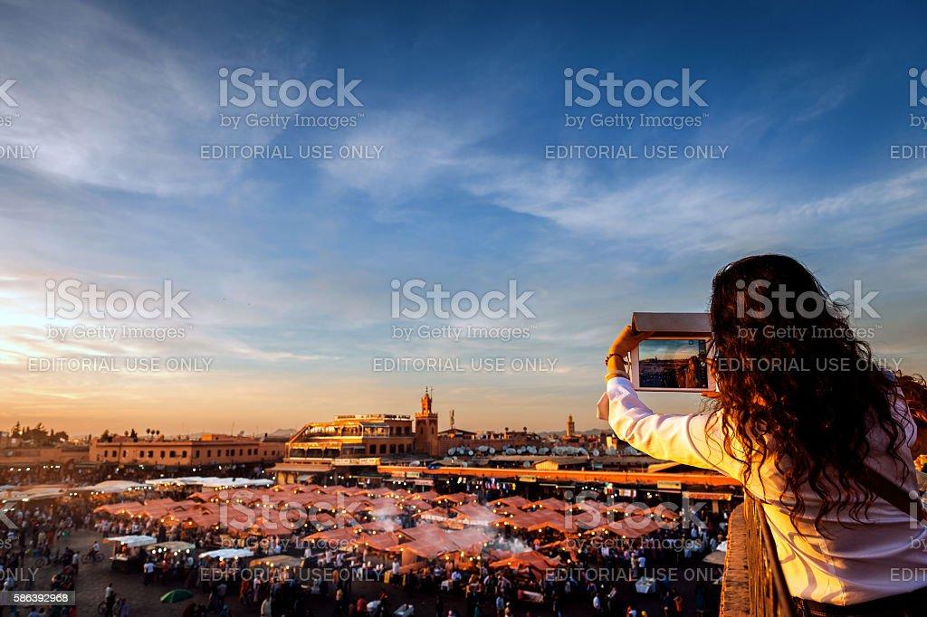 Woman photographs the market El Fna Square , Marrakech, Morocco stock photo