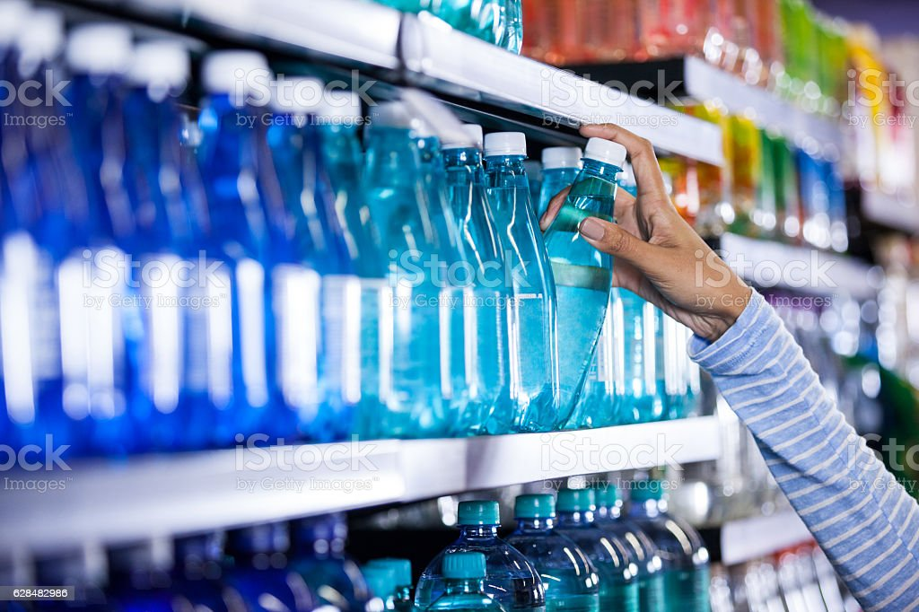 Woman picking a bottle of water stock photo