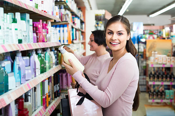 woman picking bottles with shampoo and conditioner from shelf in - drogerie stock-fotos und bilder