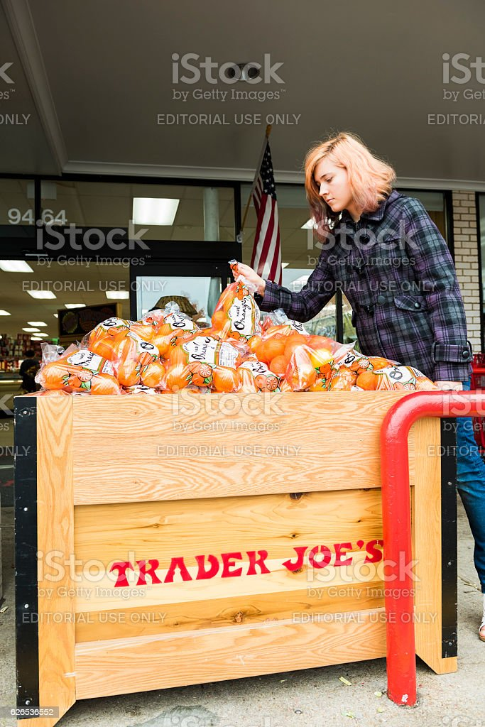 Woman picking oranges from Trader Joes grocery store by entrance stock photo