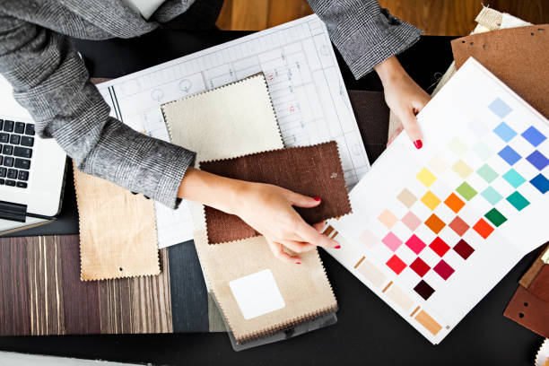Woman picking out swatches from desk stock photo