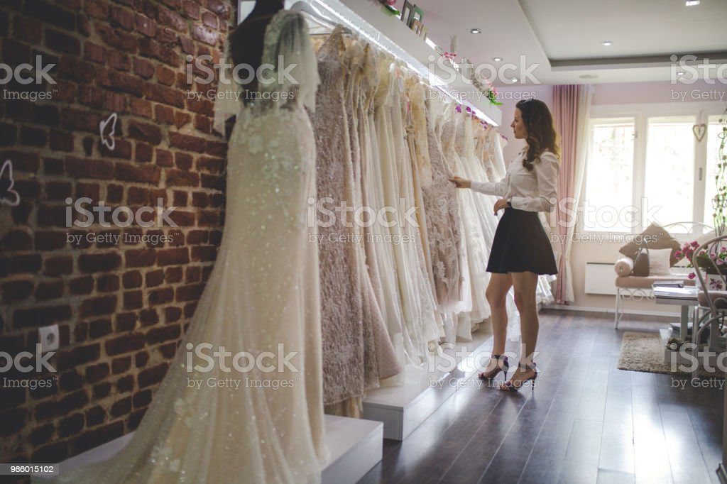 Woman picking up a perfect wedding dress stock photo